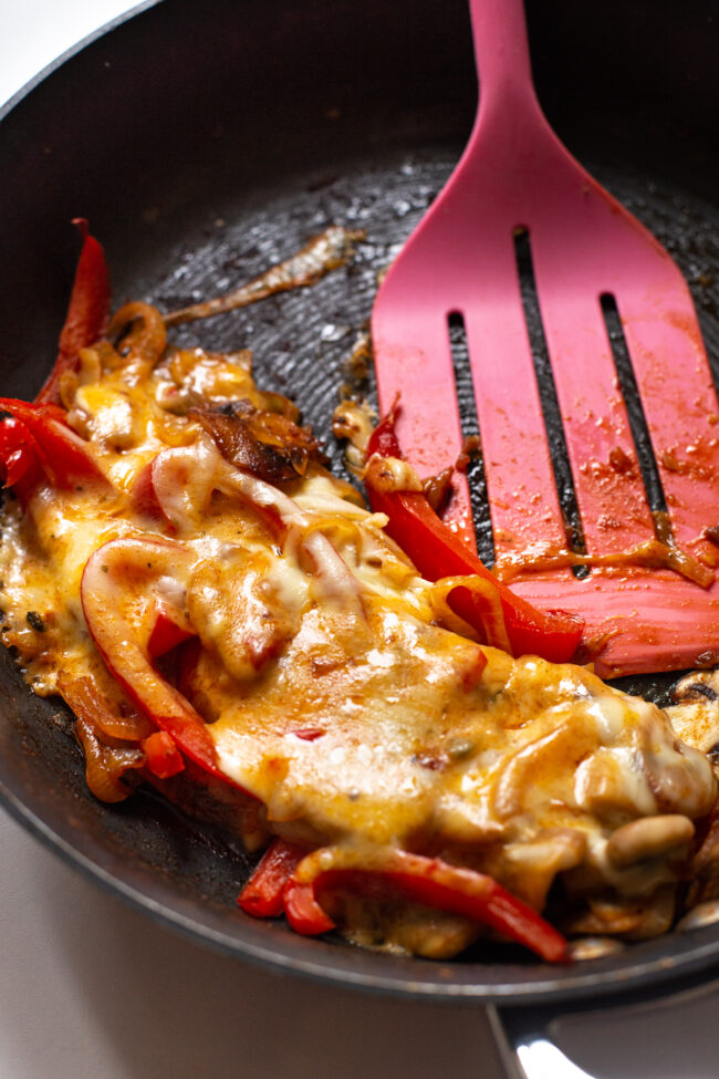 Sautéed vegetables topped with melted cheese in a frying pan.