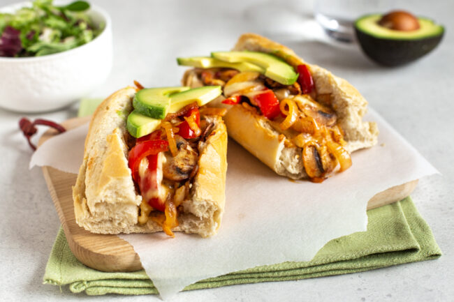 A vegetarian cheesesteak sandwich topped with melted cheese and avocado.
