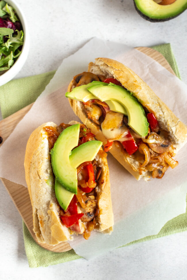 Vegetarian cheesesteak sandwiches topped with avocado and melted cheese.