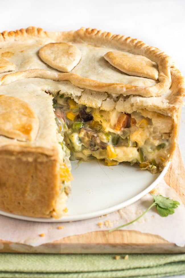 Creamy vegetable and halloumi pie with a slice removed