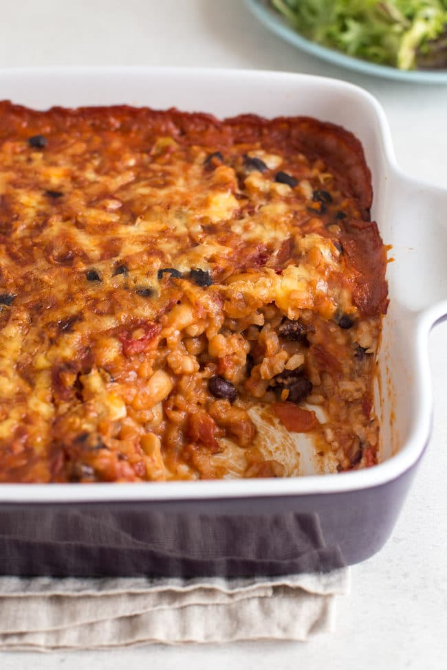 Cheese and tomato bean bake in a baking dish with a scoop removed