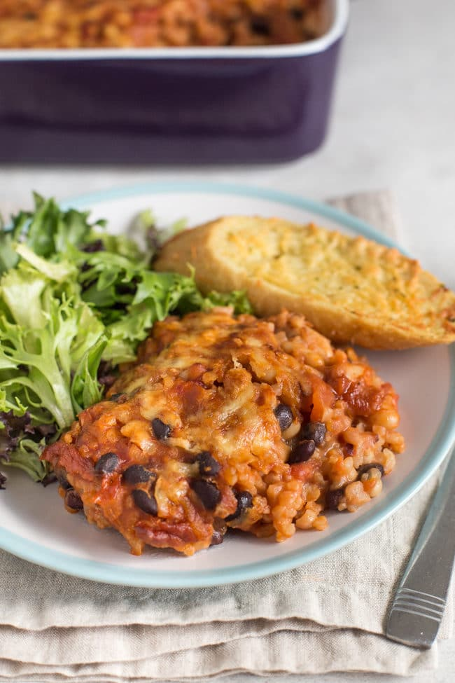 Cheese and bean bake on a plate with salad and garlic bread