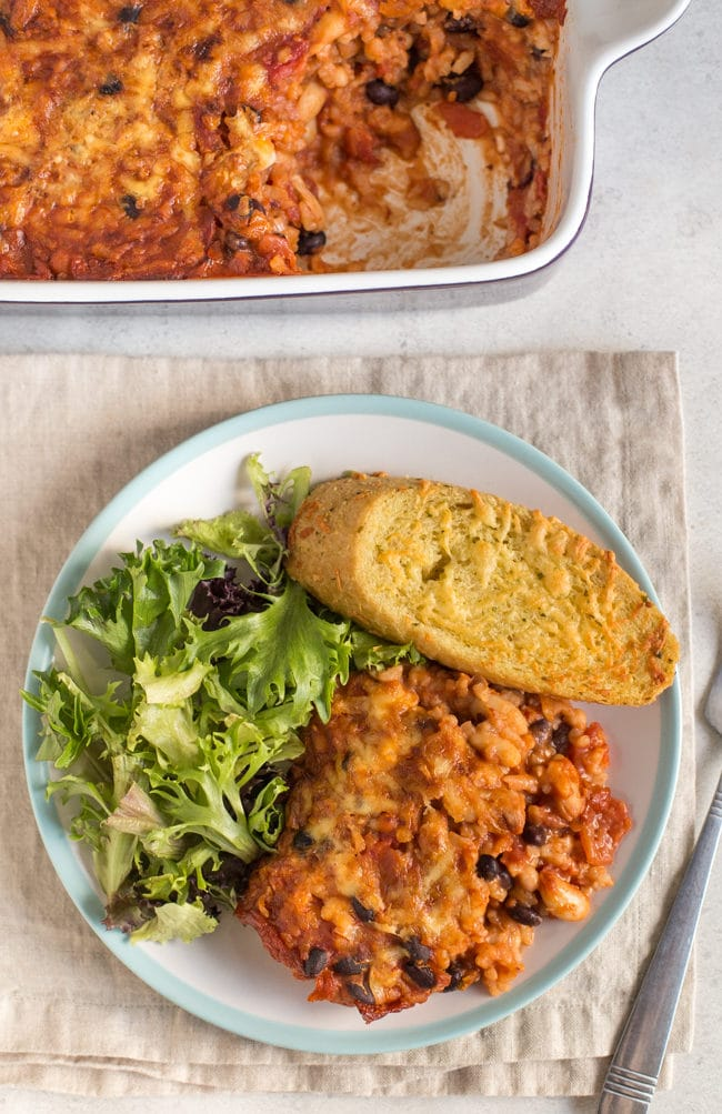 Cheese and tomato bean bake on a plate with salad and garlic bread, shot from above