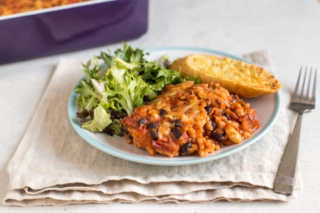 Cheese and tomato bean bake on a plate with garlic bread and salad