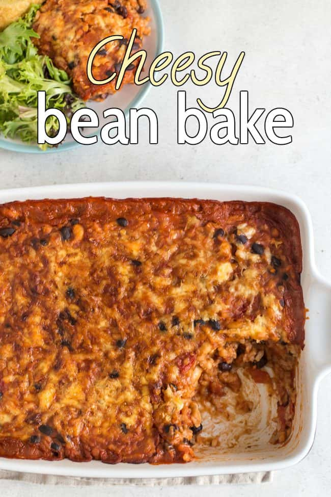 Cheese and tomato bean bake in a baking dish, with a scoop removed