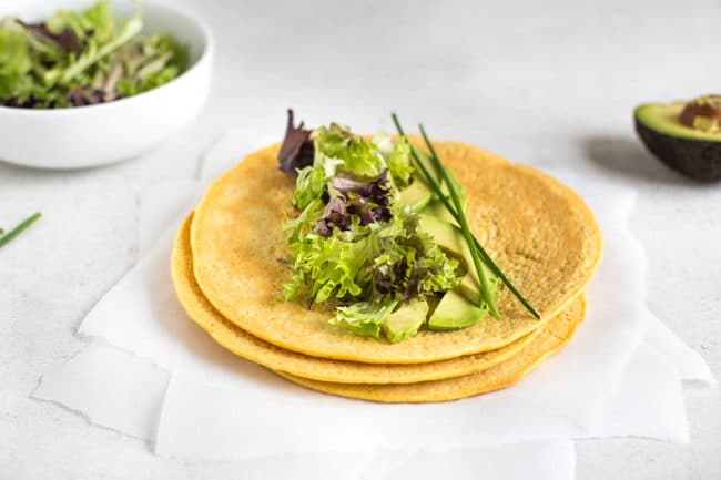 A stack of gluten-free lentil tortillas topped with lettuce and avocado, served on torn baking paper