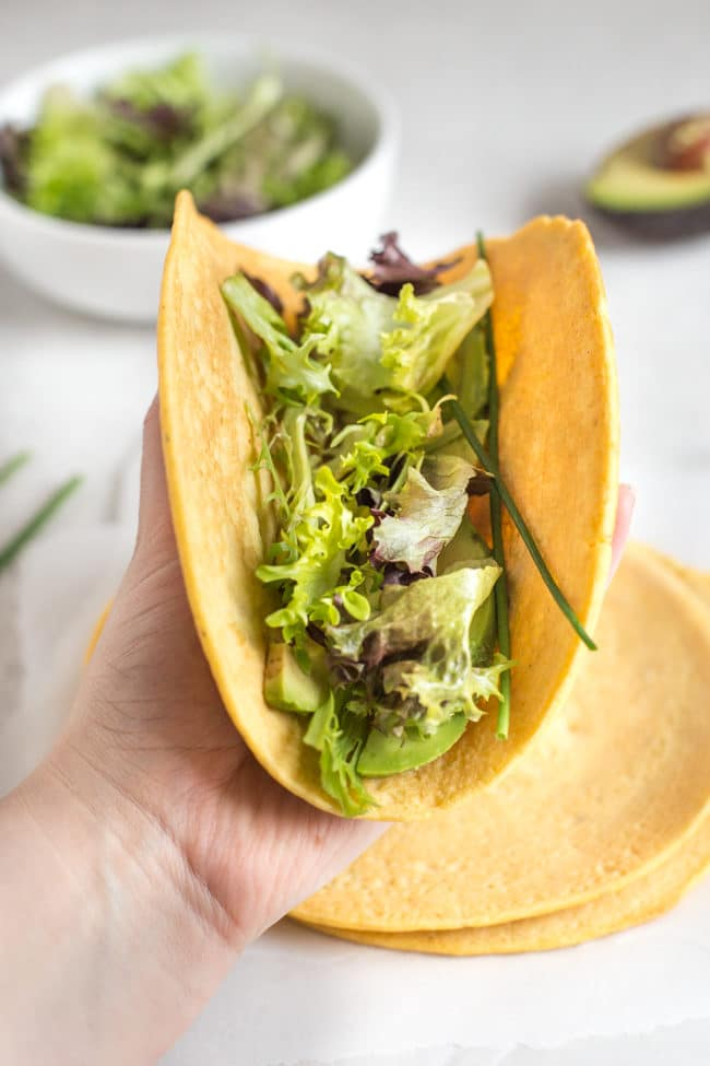 A gluten-free lentil tortilla filled with lettuce and avocado, being folded and held up by a woman's hand