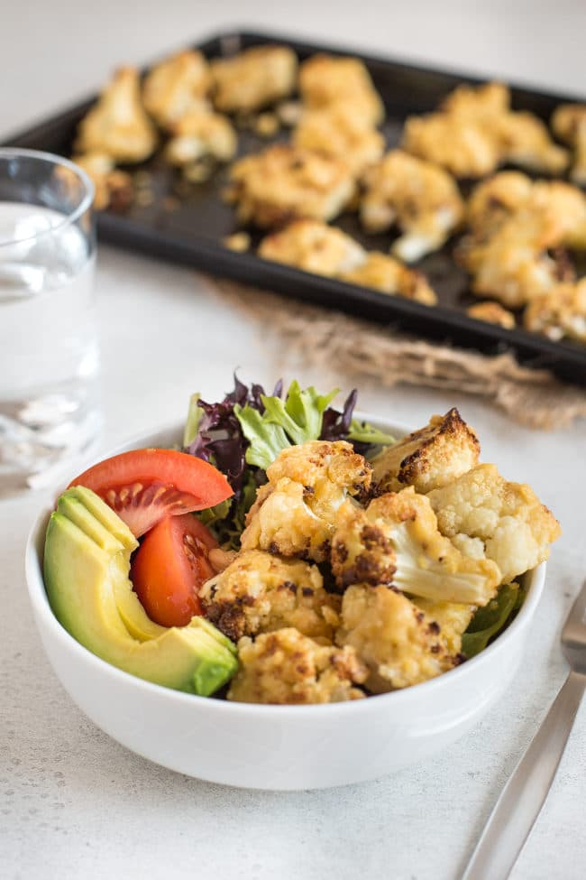 Hummus roasted cauliflower in a bowl with lettuce, tomato and avocado