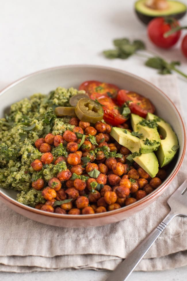 Vegan burrito bowl with quinoa and roasted chickpeas, topped with avocado and roasted tomatoes