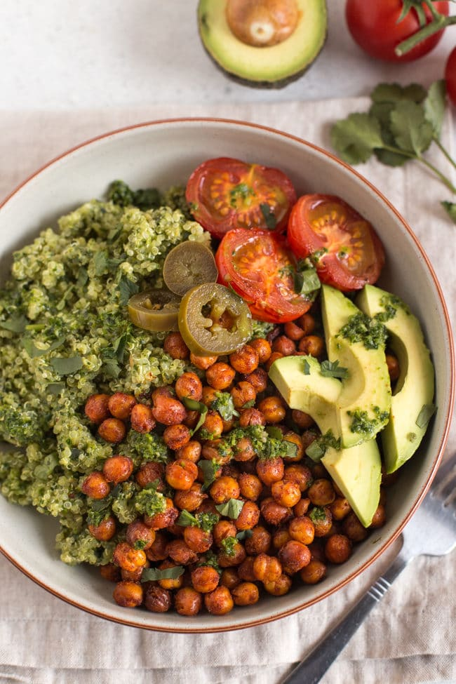 Vegan burrito bowl with quinoa and roasted chickpeas, topped with avocado and roasted tomatoes, shot from above.