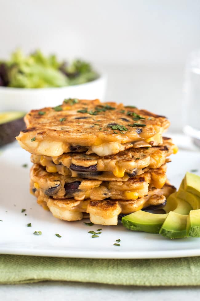 A stack of vegetarian bean and halloumi fritters on a plate with avocado