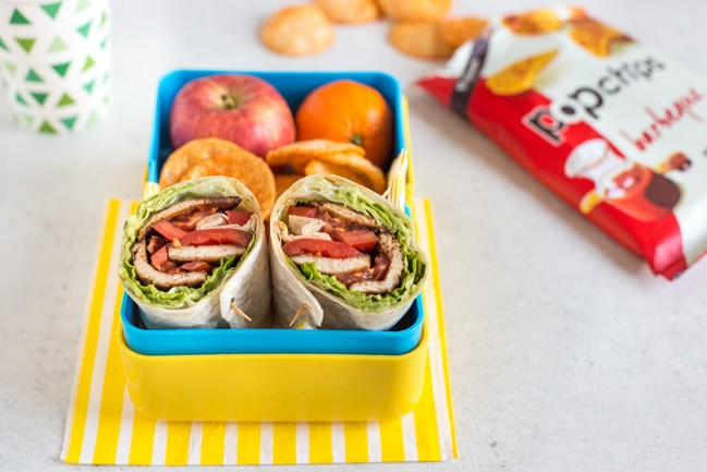 Tofu bacon BLT wraps cut in half, served in a yellow lunchbox alongside fruit and crisps