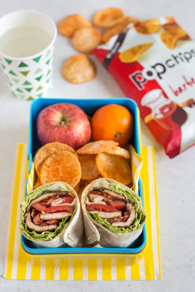 Tofu bacon BLT wraps cut in half, served in a yellow lunchbox alongside fruit and popchips