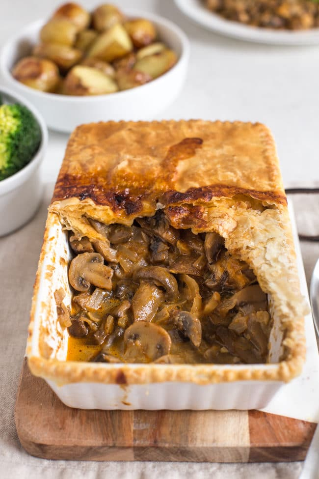 Mushroom stroganoff pie, served on a wooden board, with a scoop removed
