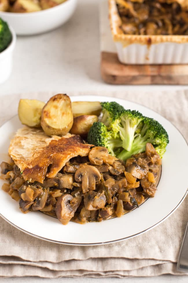A portion of mushroom stroganoff pie on a plate, served with roast potatoes and broccoli
