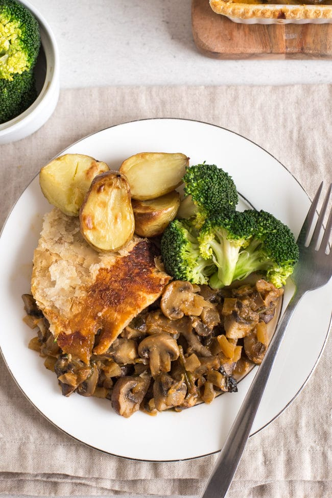 A portion of mushroom stroganoff pie on a plate, shot from above, served with roast potatoes and broccoli