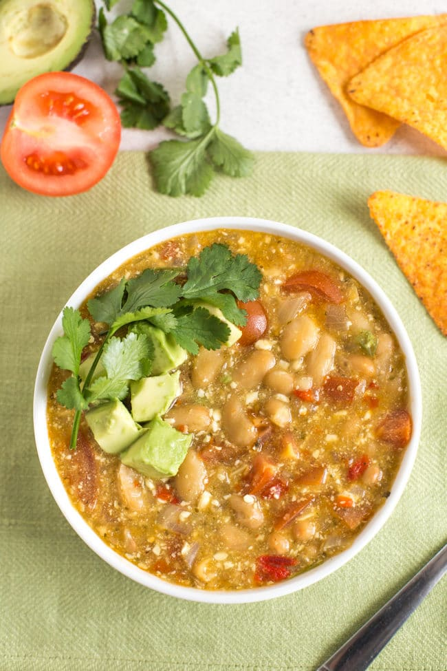 Jalapeno and white bean soup in a bowl, shot from above and topped with avocado and cilantro