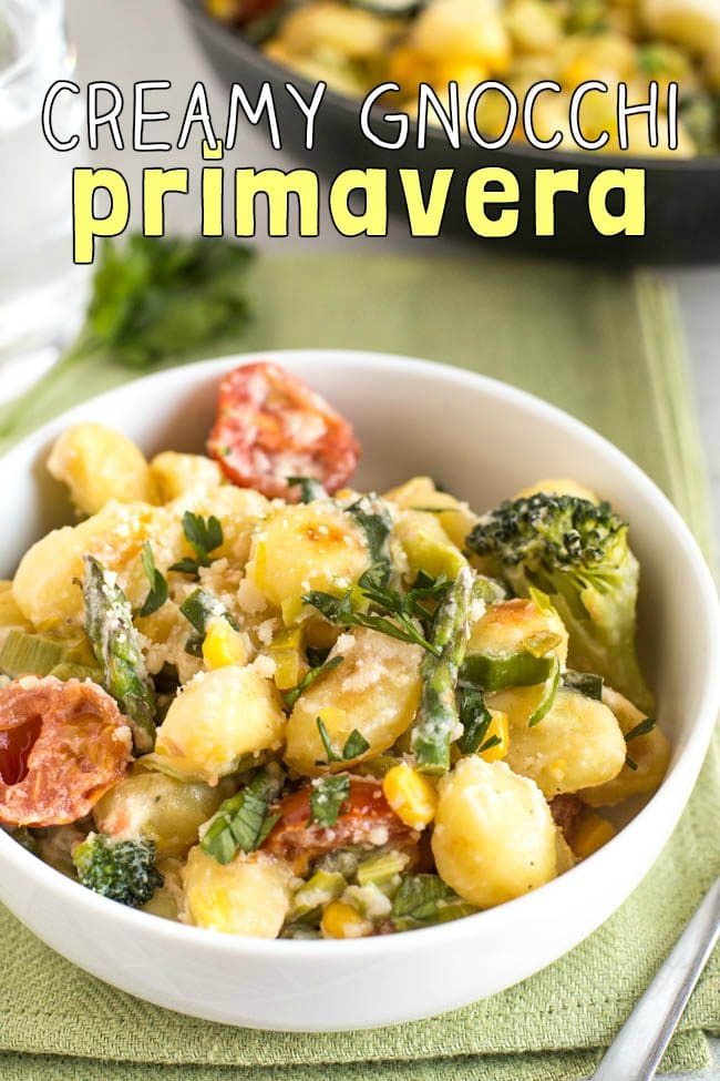 Colourful gnocchi primavera in a bowl with broccoli, asparagus and tomatoes