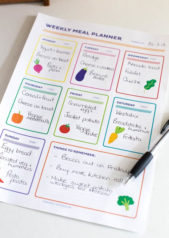Weekly meal planner printable filled in alongside a pen