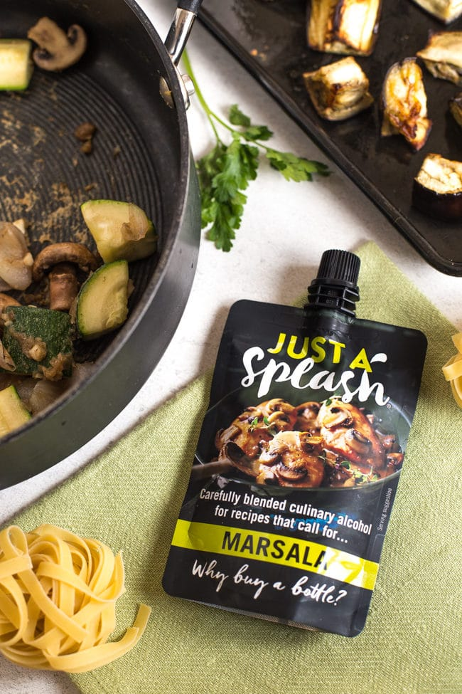 Just A Splash pouch of culinary marsala on a green napkin with pasta and vegetables