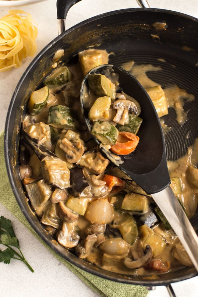 Creamy veggie marsala in a frying pan with a spoon