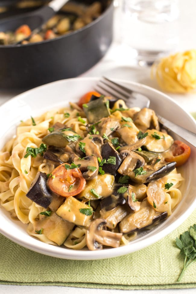 Creamy veggie marsala with tagliatelle in a white bowl with a fork