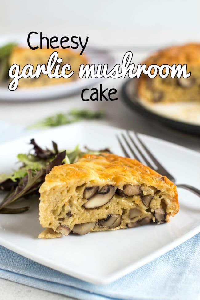 A slice of savoury garlic mushroom cake on a white plate with salad and a blue linen