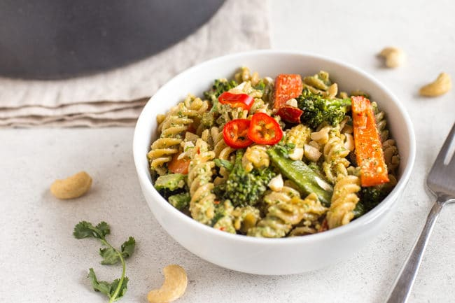 Thai pesto pasta with lots of vegetables in a white bowl