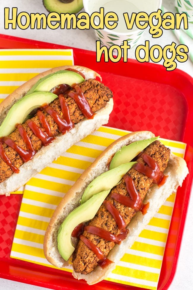 Vegan hot dogs with ketchup and avocado on a striped yellow napkin and a red tray