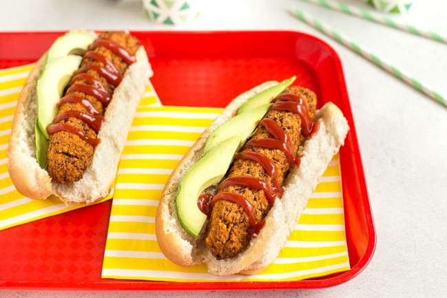 Landscape image of vegan hot dogs in buns with avocado and ketchup, served with striped yellow napkins on a red tray