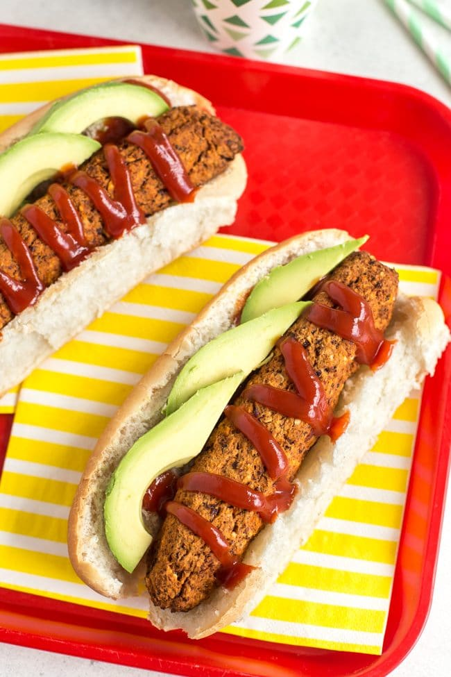 Vegan hot dogs with ketchup and avocado, served on a striped yellow napkin on a red tray