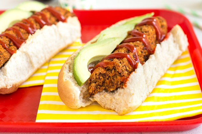 Homemade vegan hot dogs in buns with ketchup and avocado, with a bite taken