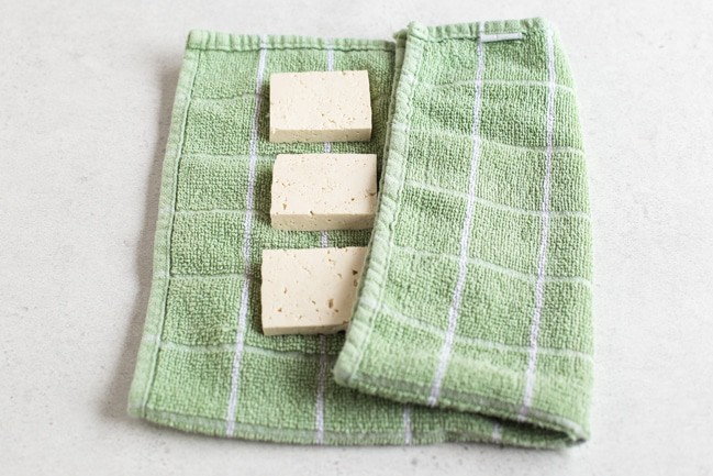 Tofu slices being covered in a green tea towel ready for pressing