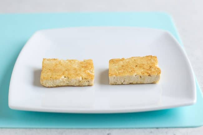 Two pieces of golden tofu on a white plate on a pale blue board