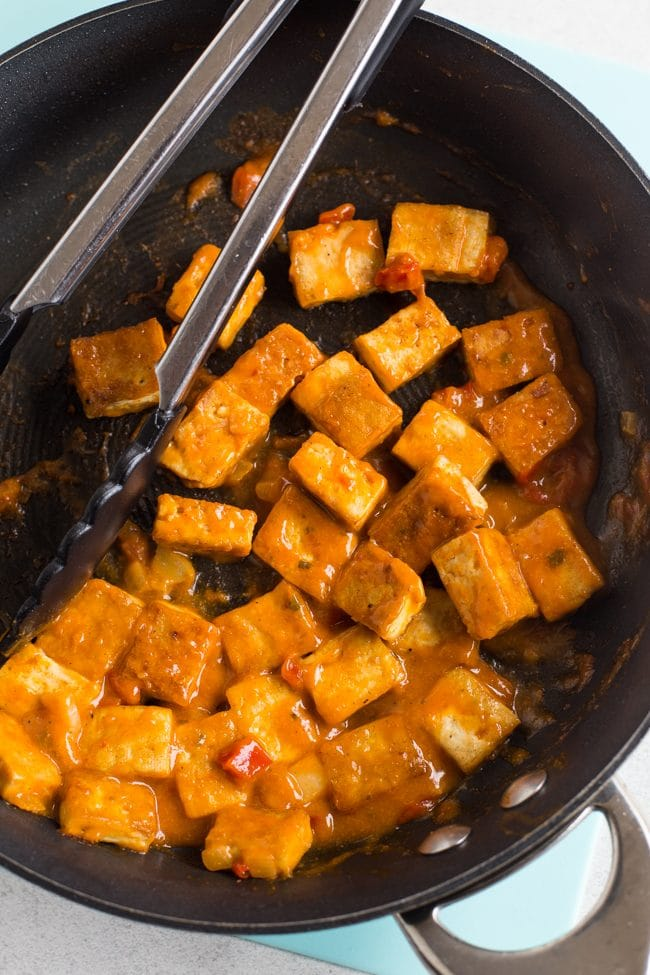 Crispy tofu cubes in a frying pan with a red Thai sauce