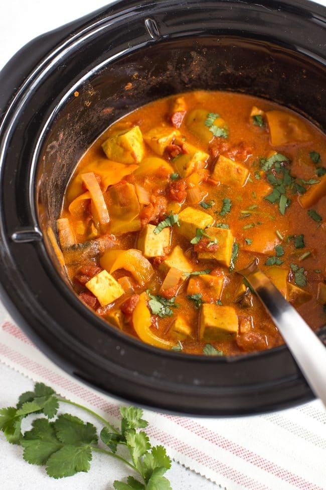 Paneer tikka masala in a slow cooker with a spoon and fresh coriander