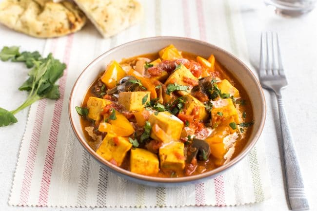 Paneer tikka masala in a bowl on a striped linen