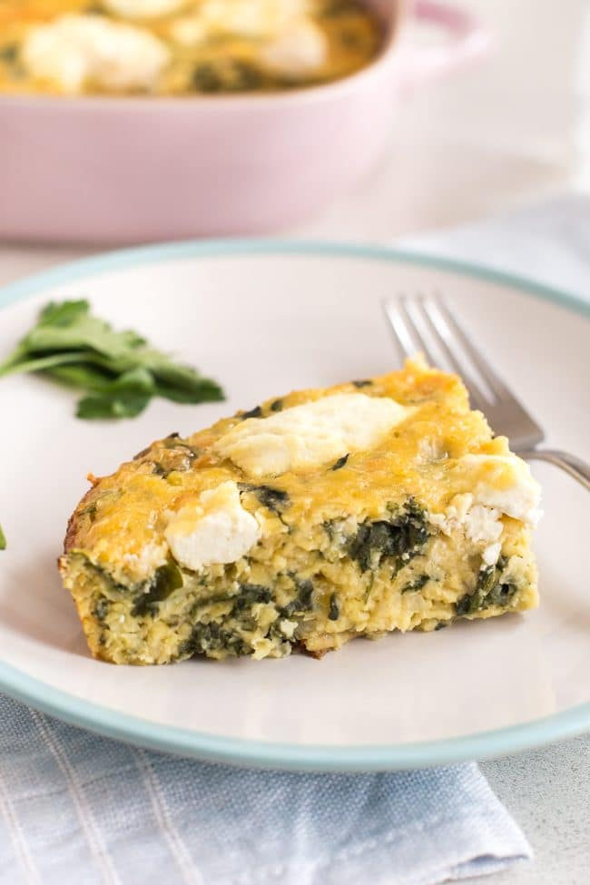 A slice of cheesy spinach and ricotta lentil slice on a plate