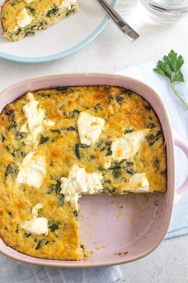 Cheesy lentil slice in a pink baking dish with a slice removed, topped with dollops of ricotta