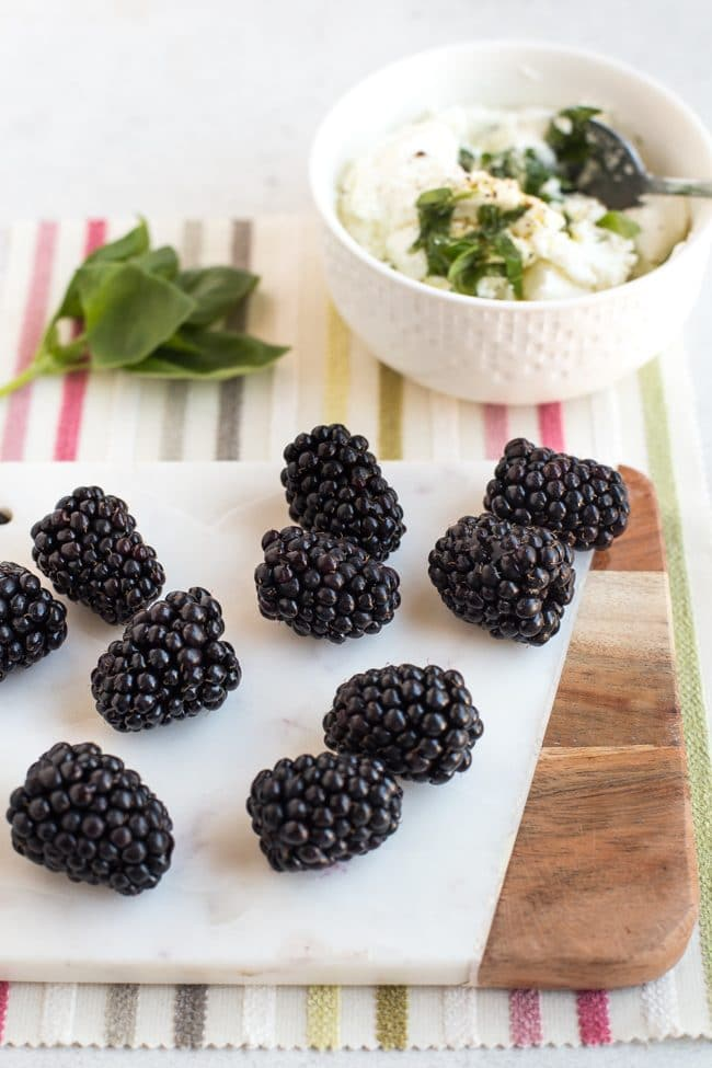 Fresh blackberries on a white board with fresh basil and goat's cheese in the background