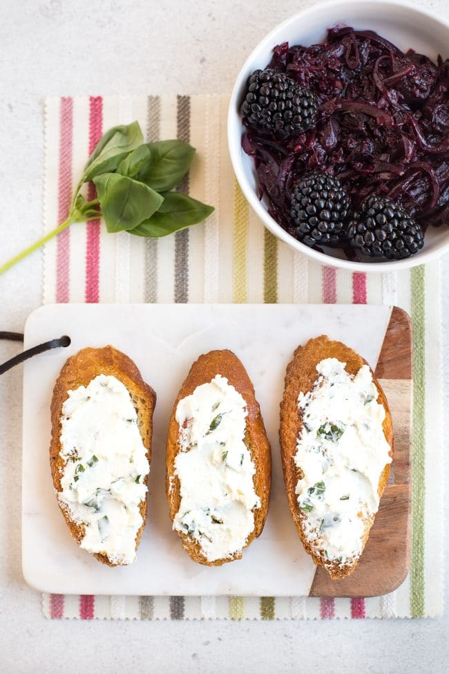 Crusty French bread spread with goat's cheese, with fresh basil and blackberry compote behind