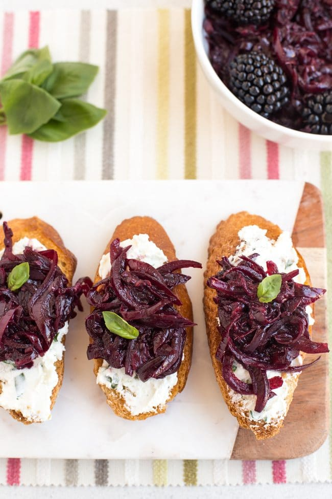 Goat's cheese crostini on a white board, topped with red onion and blackberry compote