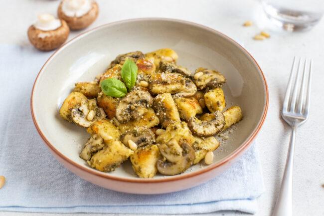 A bowlful of ricotta gnocchi with mushrooms and fresh basil.