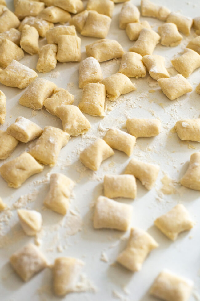 Uncooked ricotta gnocchi scattered across a white worktop.