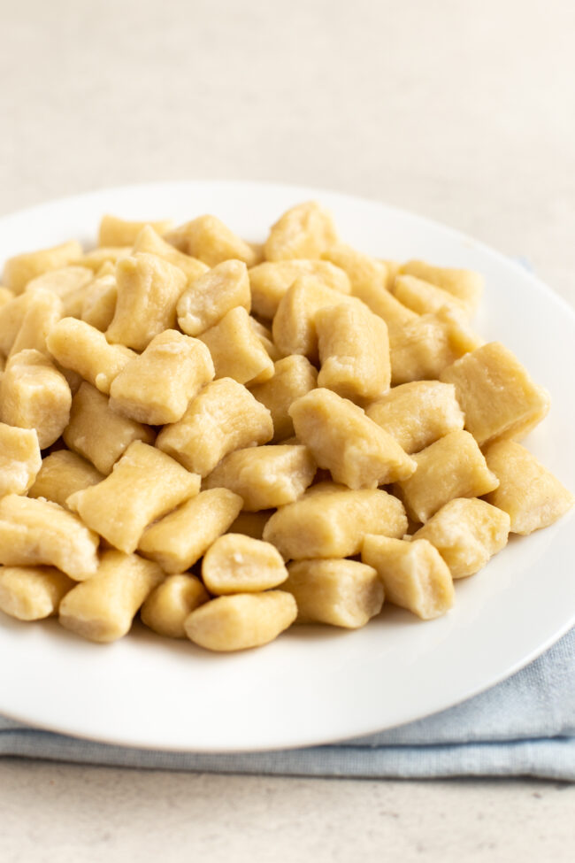 A pile of boiled ricotta gnocchi on a plate.