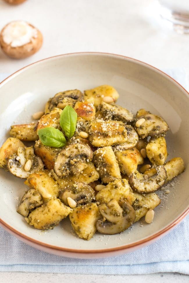 Homemade ricotta gnocchi in a bowl with pesto and garlic mushrooms