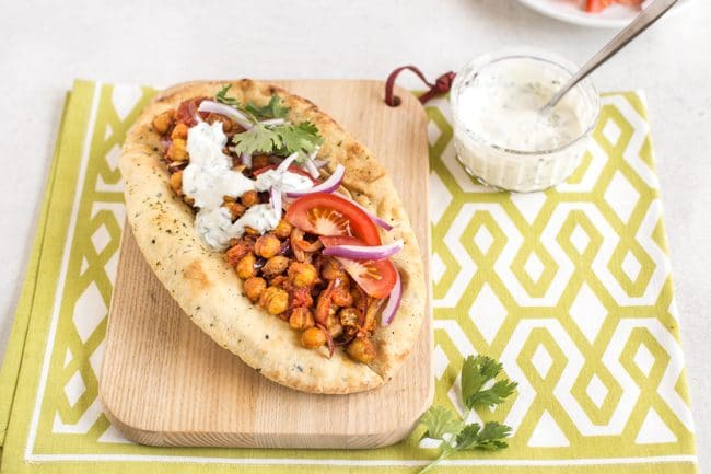 Indian roasted chickpea flatbread on a board with a green linen and a bowl of yogurt sauce