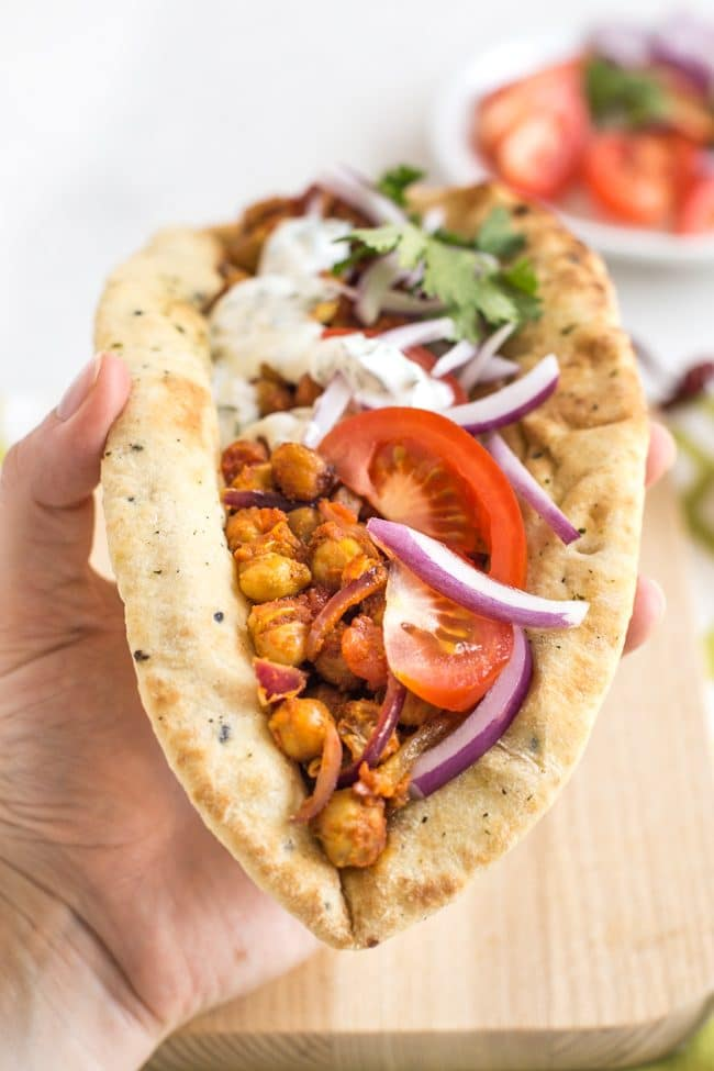 Indian roasted chickpea flatbread being held up in a hand with veggies and yogurt sauce
