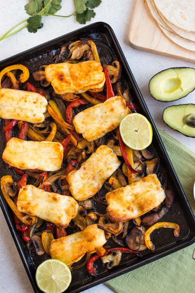 Halloumi and roasted vegetables on a sheet pan with lime and avocado
