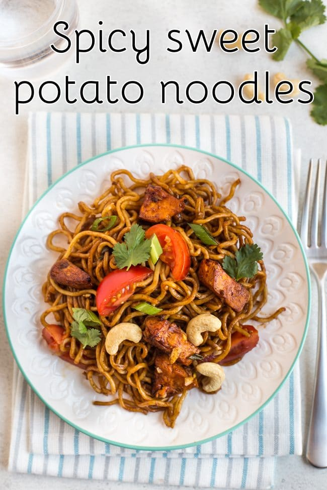 Spicy sweet potato noodles on a plate with tomatoes and cashew nuts